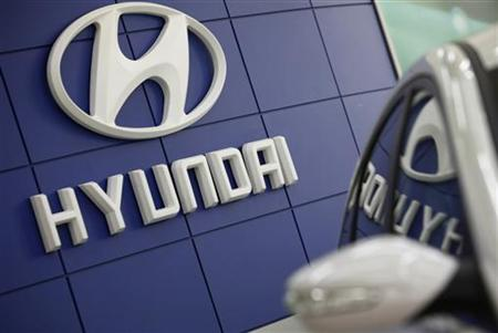 The Hyundai logo is seen next to the company's Sonata sedan at a dealership in Seoul February 24, 2010.  REUTERS/Lee Jae-Won